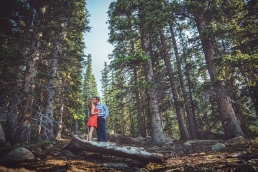 engaged couple kissing in the tall pine trees on pikes peak in colorado