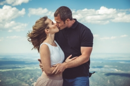 engaged couple kissing on top of a mountain at pikes peak colorado