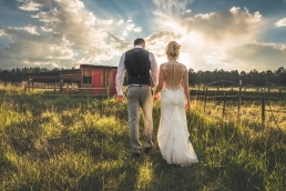 bride and groom walking towards sunset on the farm
