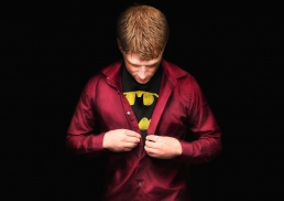 groom putting shirt on with super hero shirt under his clothes