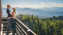 engaged couple at devils lookout in colorado looking at a view of the rockie mountains