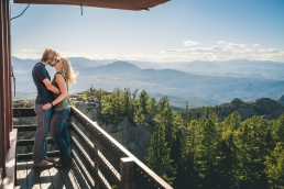 engaged couple at devils lookout in Colorado kissing in front of a view of the Rockie mountains