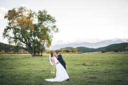 groom dipping and kissing the bride in a field with the rockie mountains in the background