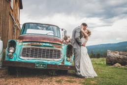 bride and groom kissing by an old truck and barn at the barn at caseys in woodland park