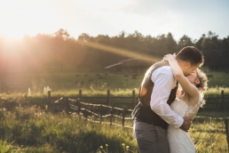 bride and groom kissing at sunset on the farm