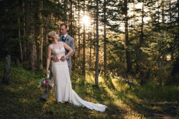 bride and groom standing in a forest in the colorado mountains