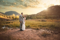 bride and groom standing at sunset in the colorado mountains