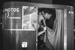 engaged couple kissing in a photobooth