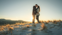 couple with foreheads together in front of sunset on top of a mountain