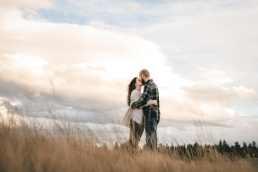 engeged couple kissing in a field with massive clouds behind them