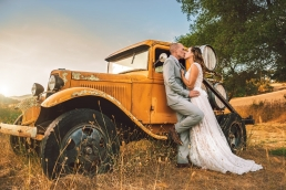 bride and groom kissing in front of a vintage antique truck with wine barrels