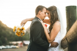 bride and groom leaning against a fence touching foreheads