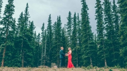 engaged couple holding hands in the forest wide shot