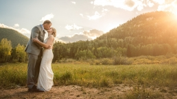 groom kissing his bride in the mountains during sunset