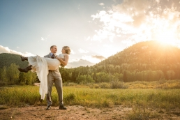 groom carrying his bride in the mountains during sunset