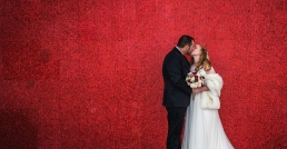 bride and groom kissing in front of a huge red tile wall at the air force academy in colorado