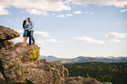 couple kissing on a cliff edge in the mountains
