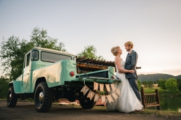 bride and groom kissing in front of an old land cruiser truck with just married written on the back
