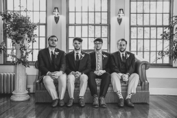 groom and groomsmen sitting on a couch