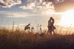 couple dancing in a field at sunset
