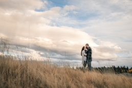 engaged couple kissing in a field in front of cool looking sky and clouds
