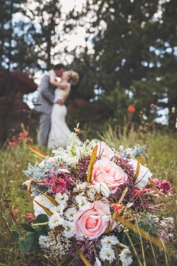 bride and groom kissing in the forest in front of the brides bouqet