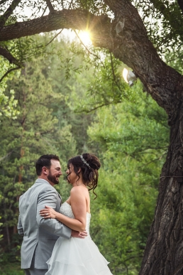 bride and groom kissing under sunset through the trees