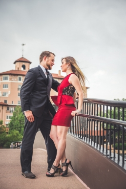 engaged couple standing on a bridge looking into each others eyes
