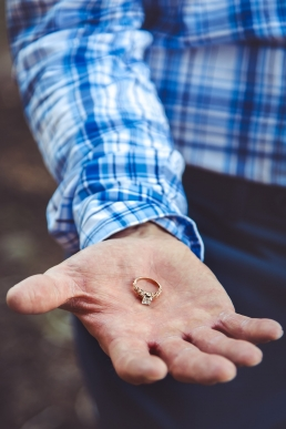 man holding an engagement ring in the palm of his hand