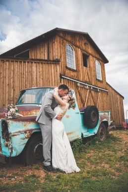 bride and groom kissing in front of an old truck and woodne barn