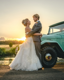 bride and groom hugging at sunset in front of a vintage toyota land cruiser