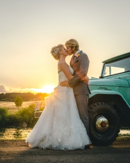 bride and groom kissing at sunset in front of a vintage toyota land cruiser