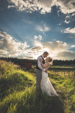 bride and groom about to kiss in front of sunset on a farm in woodland park colorado