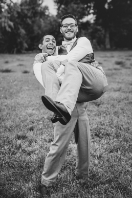 groomsman carrying the groom and laughing