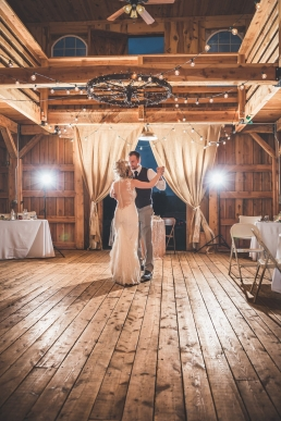 bride and groom dancing in a barn first dance