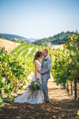 bride and groom standing in the vineyards of cloverdale california