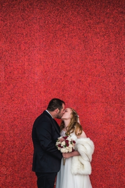 bride and groom kiss in front of a red tile wall at teh air force academy in colorado