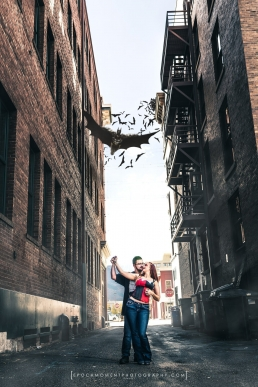 engaged couple dancing in an alley with batman flying down surrounded by bats