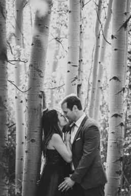 engaged couple almost kissing in the yellow aspens of colorado