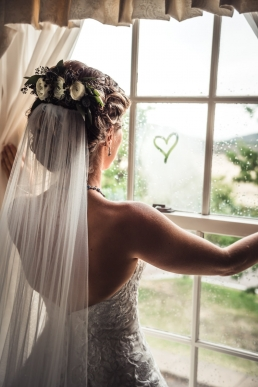bride looking the window on her wedding day with a heart drawn on the window