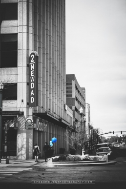 new dad birth announcement with a couple walking down a city street with blue balloons