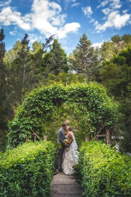 bride and groom kissing under an archway of leaves