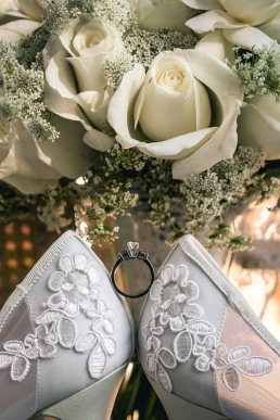 wedding ring between brides shoes and bouqet