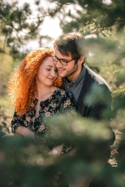 red head engaged couple sitting in the forest
