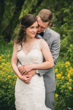 bride and groom embracing at their wedding in front of yellow flowers