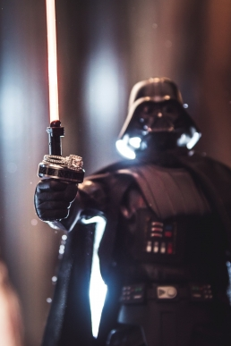 darth vader from star wars holding wedding rings on his light saber