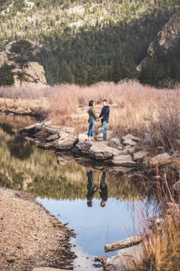 engaged couple holding hands by a river