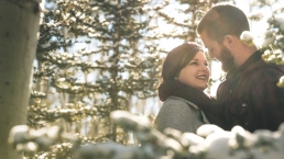 couple smiling in the aspen trees covered with snow and the sun peaking out from behind a tree