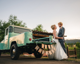 bride and groom standing in front of a vintage land cruiser