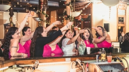 bride and bridesmaids toast with a shot